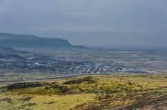 Het Landschap van IJsland met Berg, Blauwe Hemel en Stad op Achtergrond Stock Foto's