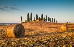 Het landschap van Toscanië met landbouwbedrijfhuis bij zonsondergang royalty-vrije stock afbeelding