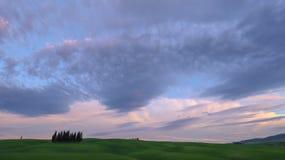 Het landschap van Val D 'Orcia: groene weiden en cipressen bij zonsondergang, Toscanië stock afbeeldingen