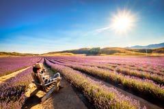 Het landschapsbeeld van een jonge toerist zit en genietend van de zonneschijn bij Lavendellandbouwbedrijf stock foto