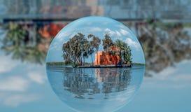 Het landschapsschot bevat een plattelandshuisje in het midden van het meer met bezinning over de kristallen bol royalty-vrije stock afbeeldingen
