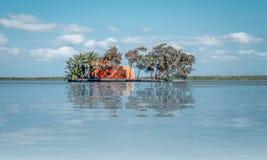 Het landschapsschot bevat een plattelandshuisje in het midden van het meer met bezinning over het water stock foto