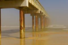 Het lange houten pijler uitrekken zich uit aan een mistige oceaanhorizon Royalty-vrije Stock Foto's