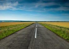 Het lange weg uitrekken zich uit in de tarwegebieden Stock Foto
