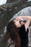 Het langharige meisje bevindt zich dichtbij een boom, die zijn hoofd opheffen Stock Afbeeldingen