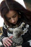 Het langharige meisje op een landbouwbedrijf kust een pluizige kip stock afbeelding