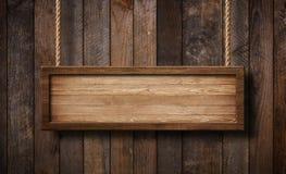 Het langwerpige houten teken hangen op kabels met houten plankenachtergrond stock fotografie