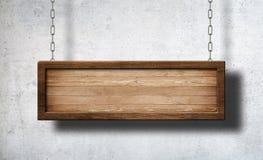 Het langwerpige houten teken hangen op kettingen met concrete muurachtergrond royalty-vrije stock foto