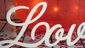 Het langzame extreme schot van de close-updia van Liefdeteken met rode harten, lichten en rode baloon op achtergrond Rood nam toe stock footage
