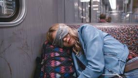 Het langzame Motie Jonge mooie meisje in de Blinddoek op de ogen, viel in slaap op de metro Hoofd gezet op een rugzak stock videobeelden