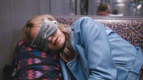 Het langzame Motie Jonge mooie meisje in de Blinddoek op de ogen, viel in slaap op de metro Hoofd gezet op een rugzak stock footage