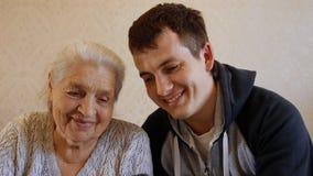 Het langzame Motieportret van de gelukkige jonge mens onderwijst zijn bejaarde grootmoeder om een smartphone te gebruiken stock video
