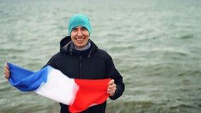 Het langzame motieportret van de opgewekte vrolijke Franse vlag houden en patriot die van Fransman overhandigt het vieren vrijhei stock videobeelden