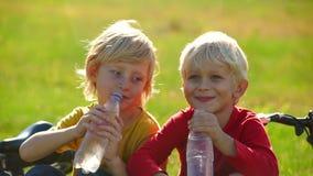 Het langzame Motieschot van twee kleine jongenscyclers zit op een gazon en drinkt water van plastic flessen Zoetwaterconcept stock video