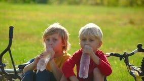 Het langzame Motieschot van twee kleine jongenscyclers zit op een gazon en drinkt water van plastic flessen Zoetwaterconcept stock footage