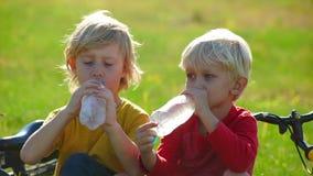 Het langzame Motieschot van twee kleine jongenscyclers zit op een gazon en drinkt water van plastic flessen Zoetwaterconcept stock videobeelden