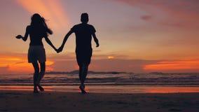 Het langzame motiesilhouet van gelukkig houdend van paar komt en gaat naar strand op zonsondergang in oceaankust samen stock video