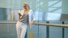 Het langzame schieten van vrouw het babbelen op telefoon in vertrekzaal stock videobeelden