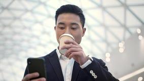 Het langzame schot van het motieportret van Aziatisch mannetje in kostuum die met een telefoon lopen stock video