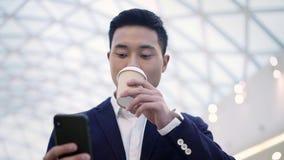 Het langzame schot van het motieportret van Aziatisch mannetje in kostuum die met een telefoon lopen stock videobeelden