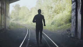 Het langzame silhouet die van de motiemens op treinsporen lopen Achter mening Abstracte achtergrond die schot beëindigen In achte stock videobeelden