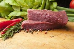 Het lapje vlees op een houten raad, sluit omhoog Stock Foto's