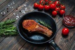 Het lapje vlees in pan en kersentomaten op lijst sluit omhoog Stock Afbeelding