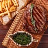 Het lapje vlees van de rundvleesbarbecue ribeye met chimichurrisaus en Franse fri Royalty-vrije Stock Foto's