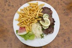Het lapje vlees van de varkensvleeskraag met koolsalade, kruidboter, frieten Stock Afbeelding