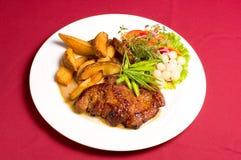 Het lapje vlees van het varkensvlees met aardappelen in de schil Royalty-vrije Stock Foto