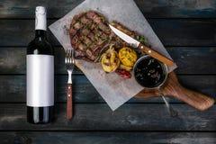 Het lapje vlees van het riboog bij het koken van document of perkament op houten bureau met groenten en kruidengrens op gekleurde stock foto's