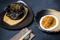 Het lapje vlees van het rundvleeshaasbiefstuk dat met een bijgerecht van gebakken bataat, zwarte achtergrond wordt geroosterd royalty-vrije stock foto