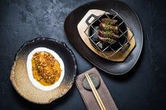 Het lapje vlees van het rundvleeshaasbiefstuk dat met een bijgerecht van gebakken bataat, zwarte achtergrond wordt geroosterd stock afbeeldingen