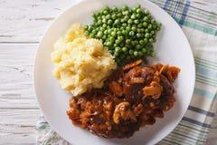 Het lapje vlees van Salisbury met aardappels en groene erwtenclose-up horizonta Royalty-vrije Stock Foto's
