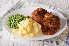 Het lapje vlees van Salisbury met aardappels en groene erwtenclose-up op een plaat Stock Fotografie