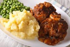 Het lapje vlees van Salisbury met fijngestampte aardappels en groene erwtenclose-up  Stock Fotografie