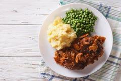 Het lapje vlees van Salisbury met jus, fijngestampte aardappels en groene erwten Hori Stock Afbeeldingen