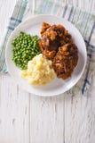 Het lapje vlees van Salisbury met jus, fijngestampte aardappels en groene erwten Vert Stock Foto's