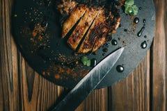 Het lapje vlees van het varkensvleesbeen op een raads houten achtergrond met kenzy honing, peper stock afbeelding