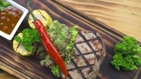 Het lapje vleessamenstelling van het barbecuevlees Geroosterd lapje vlees met roodgloeiende peper, kruid, graan en tomatensaus op stock videobeelden
