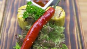 Het lapje vleessamenstelling van het barbecuevlees Geroosterd lapje vlees met roodgloeiende peper, kruid, graan en tomatensaus op stock video