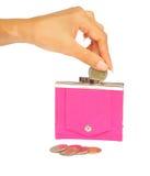 Het laten vallen van een muntstuk in een roze beurs Royalty-vrije Stock Afbeeldingen