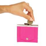 Het laten vallen van een muntstuk in een roze beurs Royalty-vrije Stock Fotografie