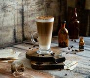 Het Latteglas met gelaagd latte, de cappuccino of mocha op houten raad bevinden zich op grijze rustieke lijst royalty-vrije stock fotografie