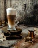 Het Latteglas met gelaagd latte, de cappuccino of mocha op houten raad bevinden zich op grijze rustieke lijst royalty-vrije stock afbeeldingen