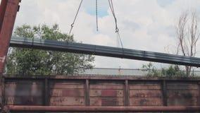 Het leegmaken van de profielpijp door een brugkraan van een goederenwagon, ladingenmetaal in een pakhuis, een grote brugkraan