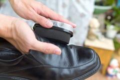 Het leer zwarte schoenen van het handenpoetsmiddel royalty-vrije stock foto's