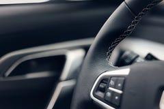 Het leerstuurwiel van verschillende media in een moderne dure auto Geperforeerd leerstuurwiel stock foto