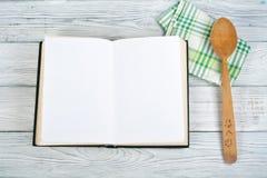 Het lege boek van de receptenkok op houten achtergrond, lepel, deegrol, geruit tafelkleed royalty-vrije stock foto's