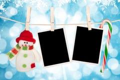 Het lege fotokaders en sneeuwman hangen op de drooglijn Stock Foto